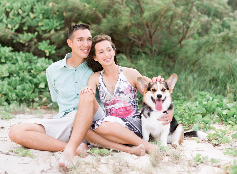 Best Oahu Photographer | Honeymoon Couple sitting on beach with Corkie dog